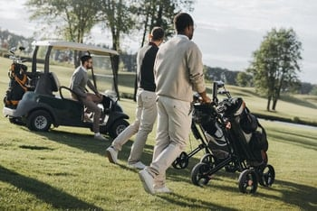 Golfers using a push cart