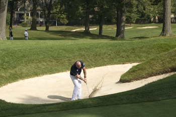 Marine Corps Gunnery Sgt. Matthew Branch using a sand wedge in a sand trap