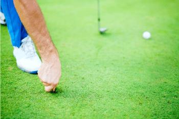 Golfer using divot repair tool