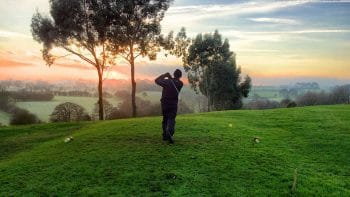 Golfer with best golf jacket at dusk