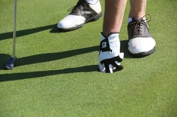 Golfer wearing shoes and getting the ball out of hole after put