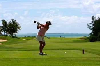 Best Golf Balls for High Handicappers & Beginners with a woman teeing off in a beautiful beach setting