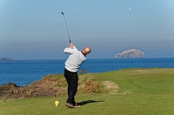 golfer launching golf ball in front of portable golf launch monitor